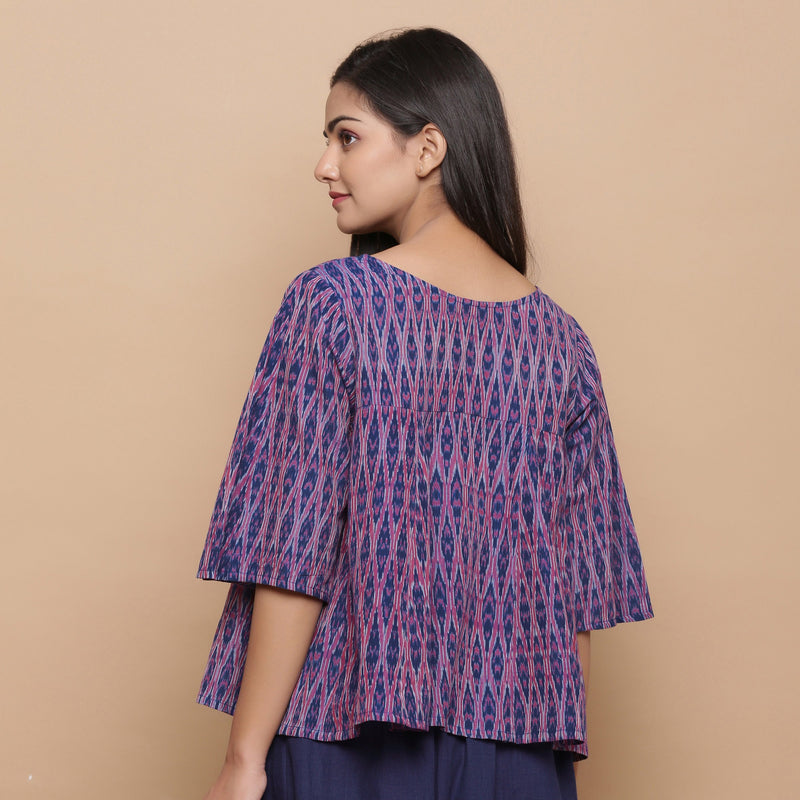 Back View of a Model wearing Blue Ikat Boat Neck Flared Godet Top