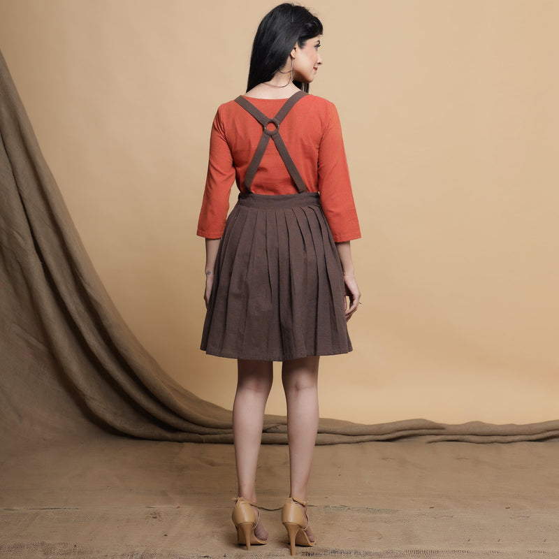 Back View of a Model wearing Brown Pleated Criss-Cross Back Dress