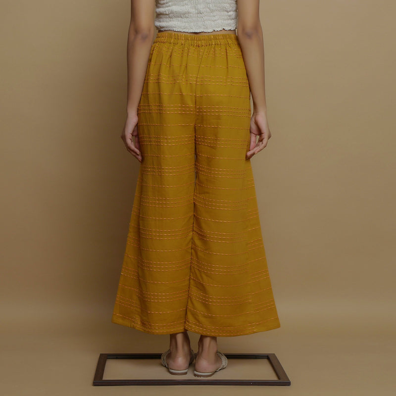 Back View of a Model wearing Mustard Paneled Striped Handwoven Pant
