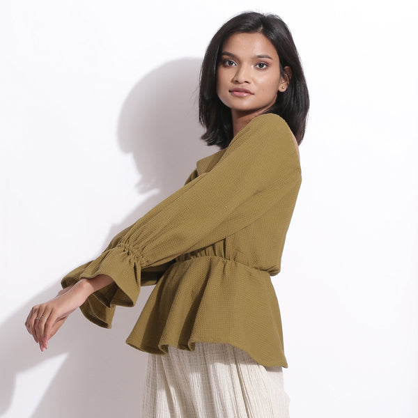 Left View of a Model wearing Cotton Waffle Olive Green Peplum Top