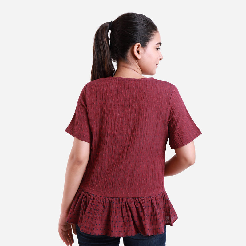 Back View of a Model wearing Crimson Crinkled Cotton Polka Dot Peplum Top