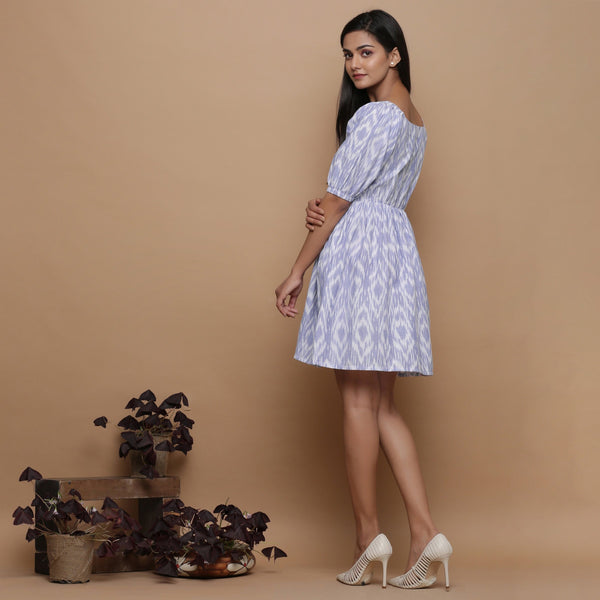 Left View of a Model wearing Powder Blue Ikat Elasticated Gathered Dress