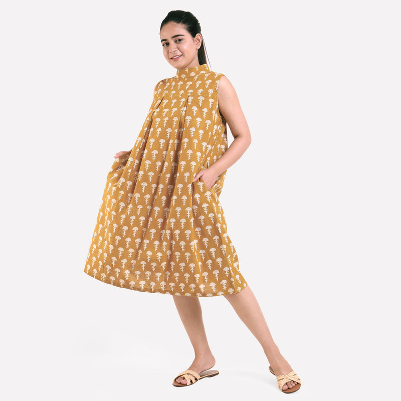 Left View of a Model wearing Bagru Block Print Mustard Pleated Dress