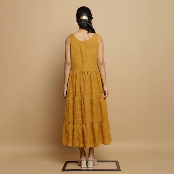 Back View of a Model wearing Mustard Handwoven Gathered Tier Dress