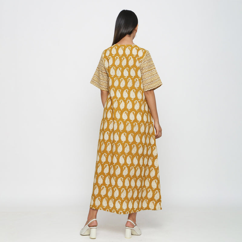 Back View of a Model wearing Mustard Block Printed Snug Dress