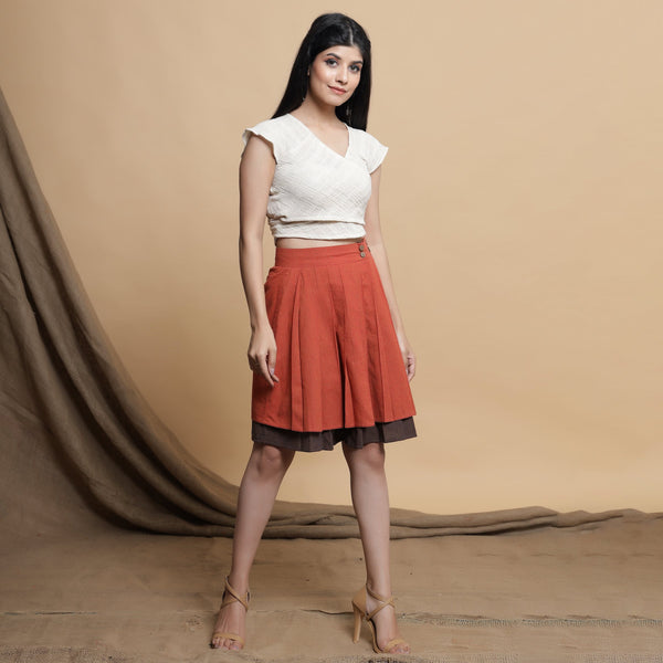 Right View of a Model wearing Orange and Brown Reversible Pleated Flared Skirt