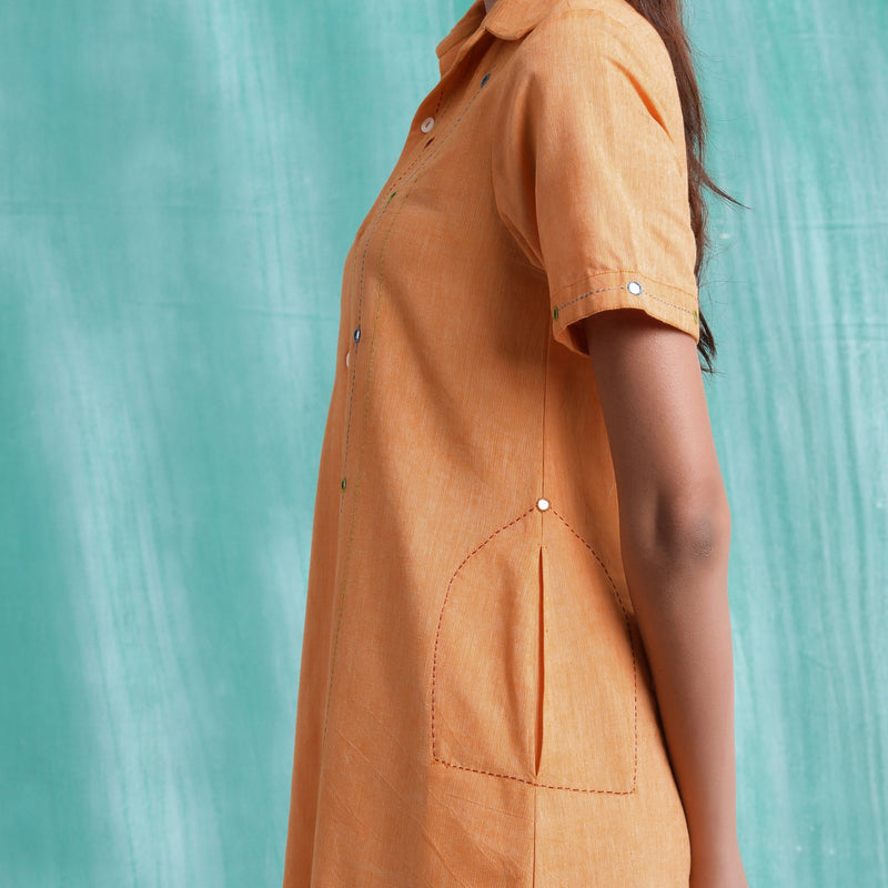 Left View of a Model wearing Orange Mirrored Asymmetrical Shirt Dress
