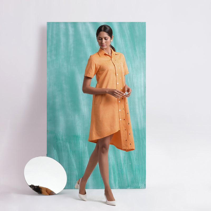 Right View of a Model wearing Orange Mirrored Asymmetrical Shirt Dress
