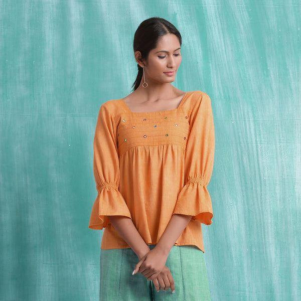 Front View of a Model wearing Orange Handspun Yoked Mirror Top