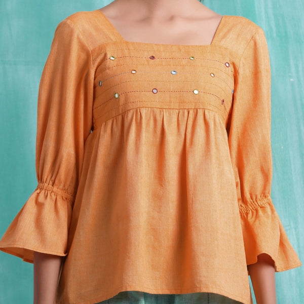 Front Detail of a Model wearing Orange Handspun Yoked Mirror Top