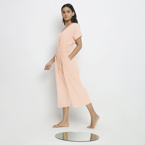 Left View of a Model wearing Powder Pink Vegetable Dyed Button-Down Jumpsuit
