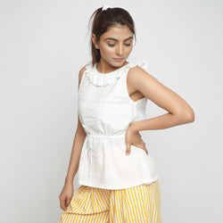 Left View of a Model wearing Ruffled Off-White Peplum Top