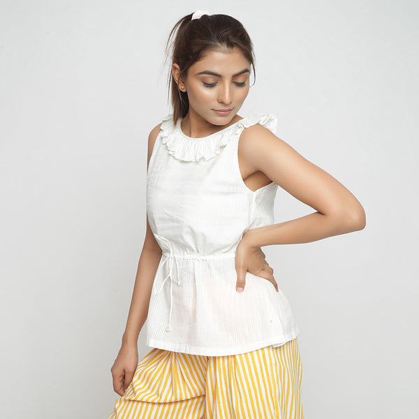 Left View of a Model wearing Ruffled Off-White Cotton Peplum Top