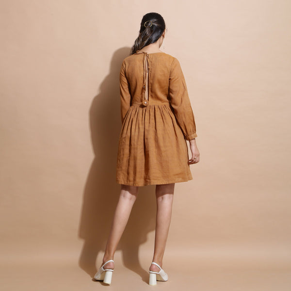 Back View of a Model wearing Rust Handspun Solid Gathered Dress