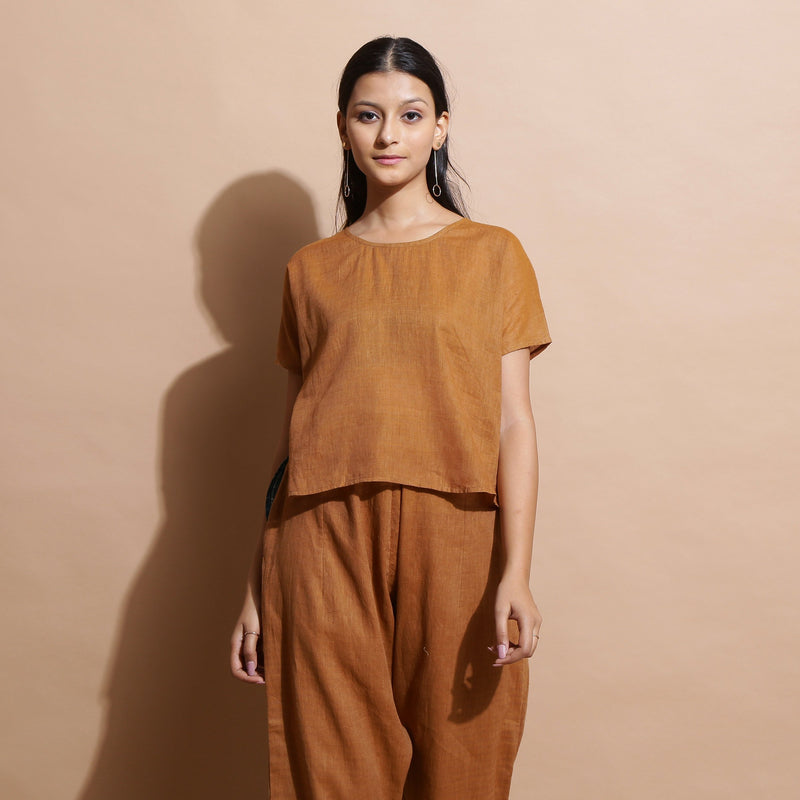 Front View of a Model wearing Rust Cotton Muslin Lined High Low Top