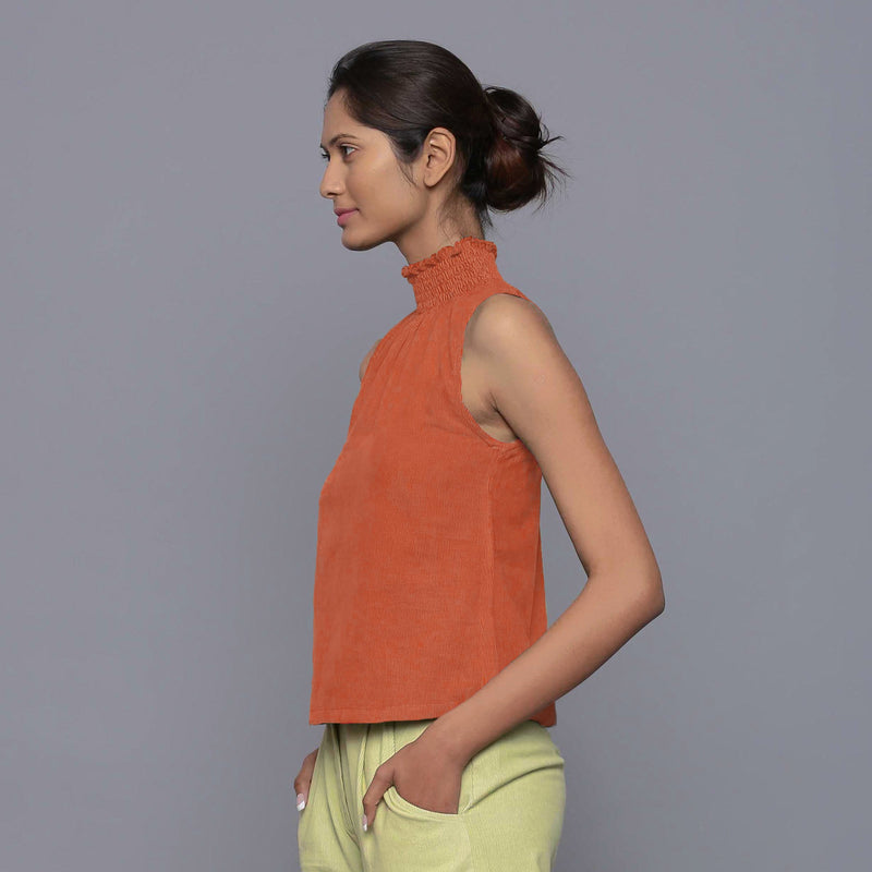 Left View of a Model wearing Sunset Rust Cotton Corduroy High Neck Top
