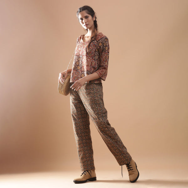 Left View of a Model wearing Warm Muddy Green Kalamkari Straight Pants