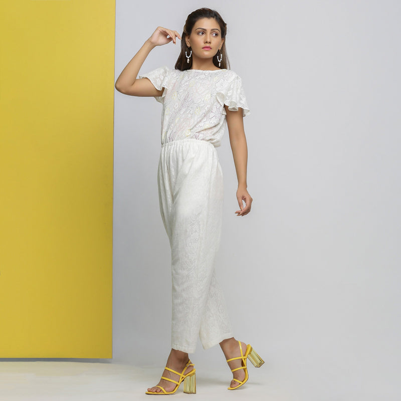 Left View of a Model wearing White Cotton Lace Hand Embroidered Jumpsuit