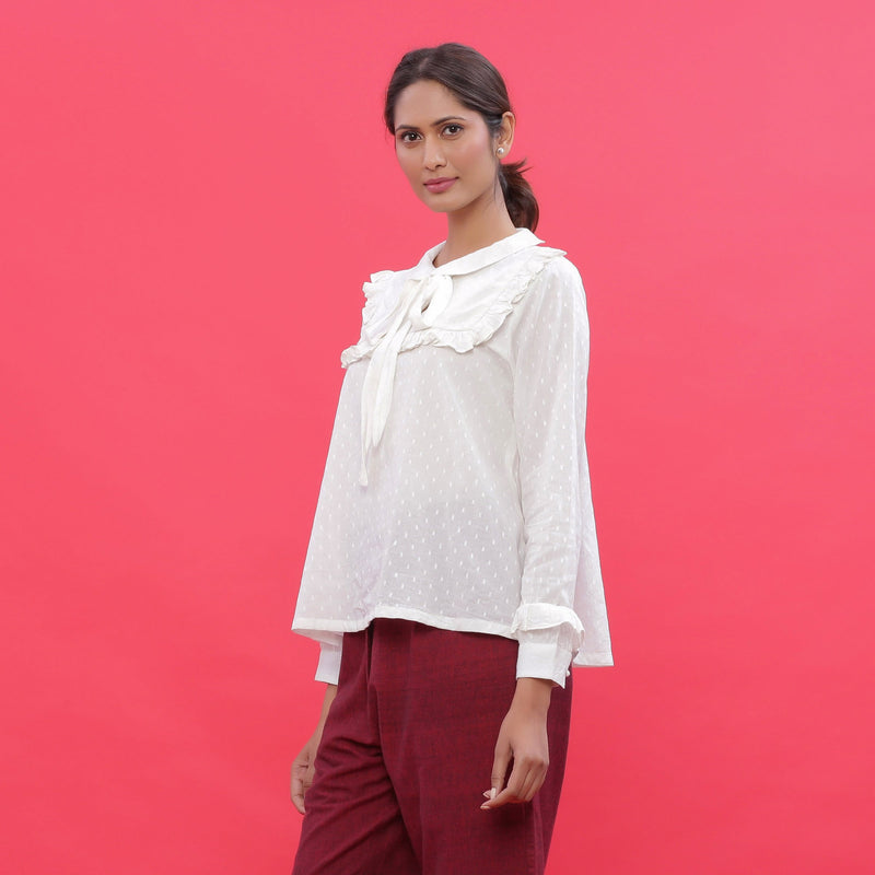 Left View of a Model wearing White Dobby Ruffled Peasant Blouse Top