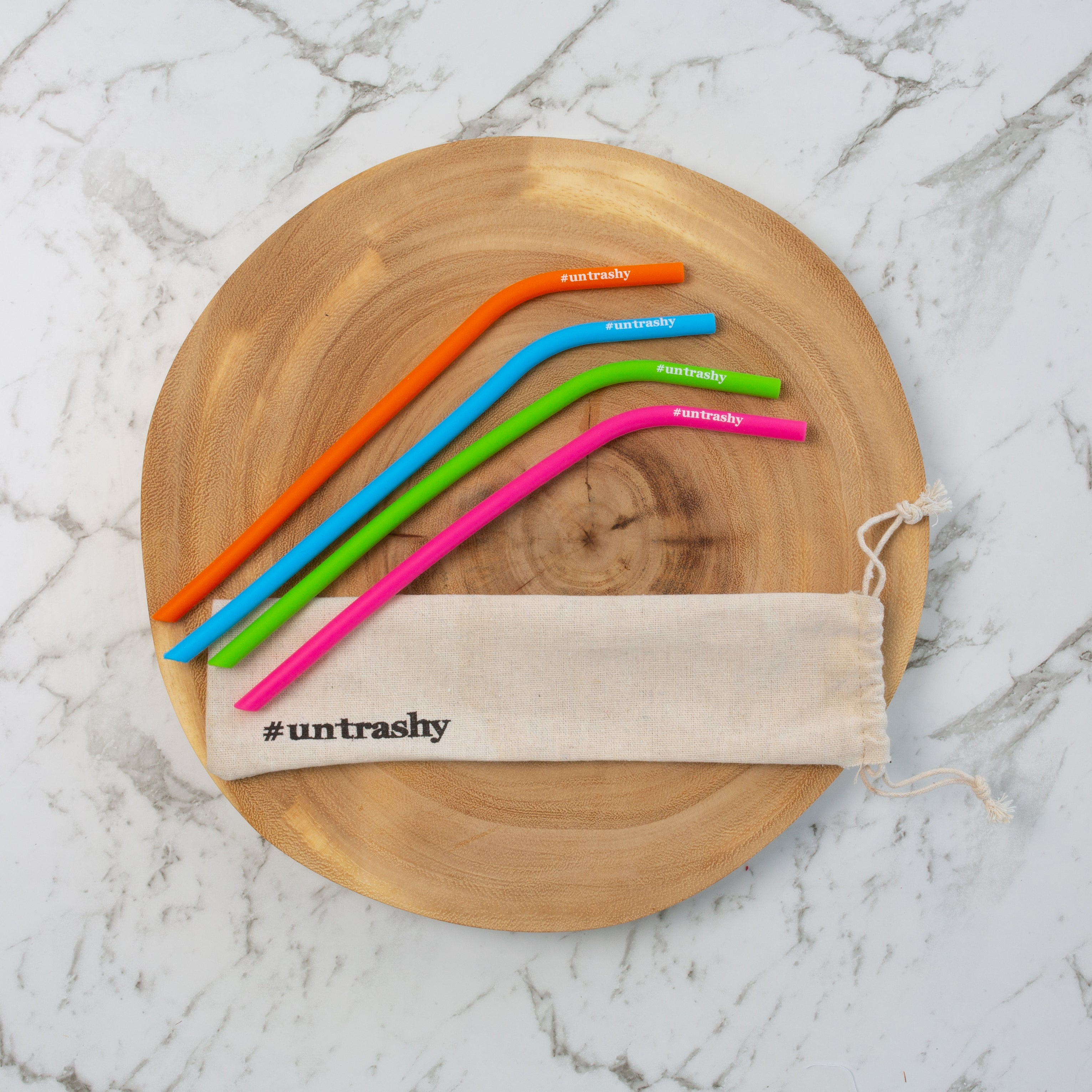 colourful silicone straws with a straw bag on a wooden board