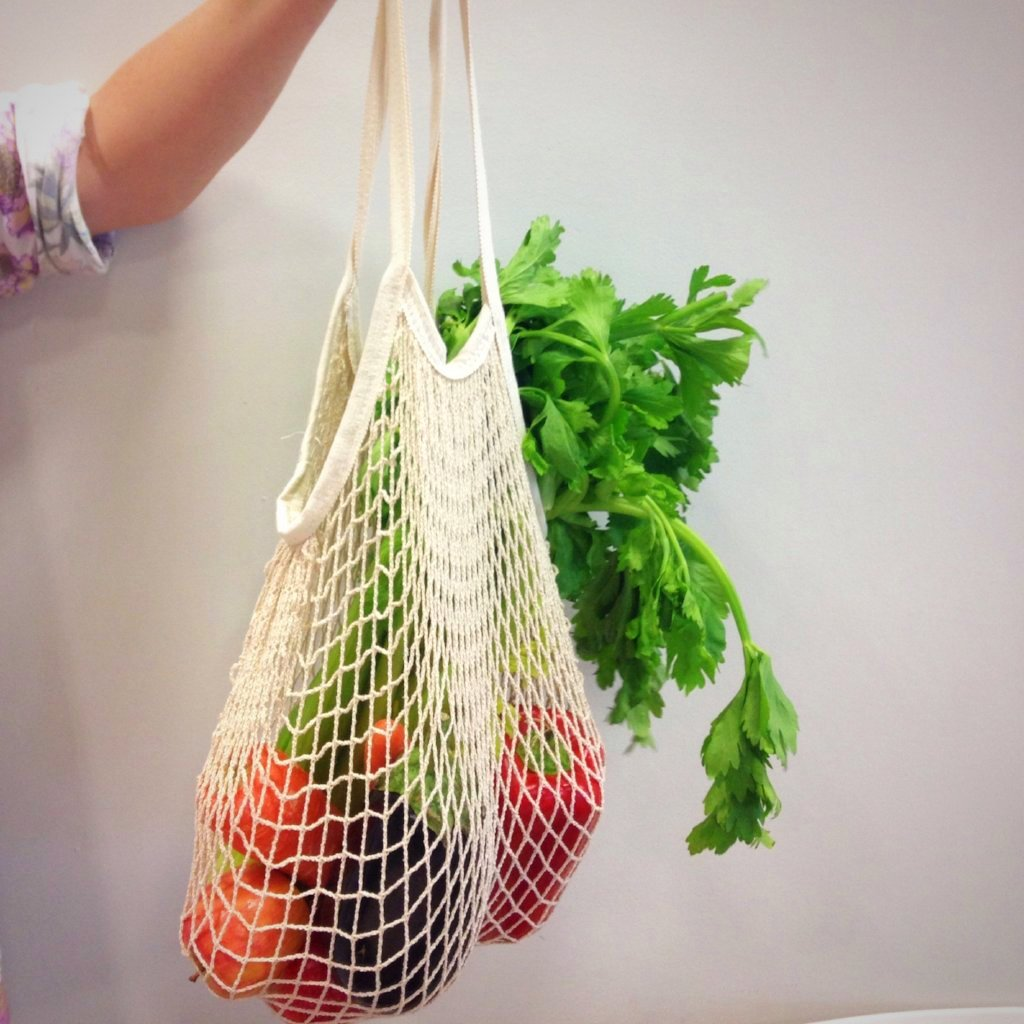 woman's arm holding a reusable string bag containing fresh vegetables