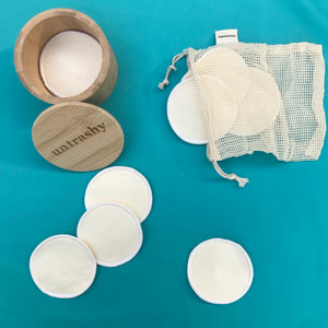 calico and organic cotton make-up remover pads with a wash bag and a box on a teal background