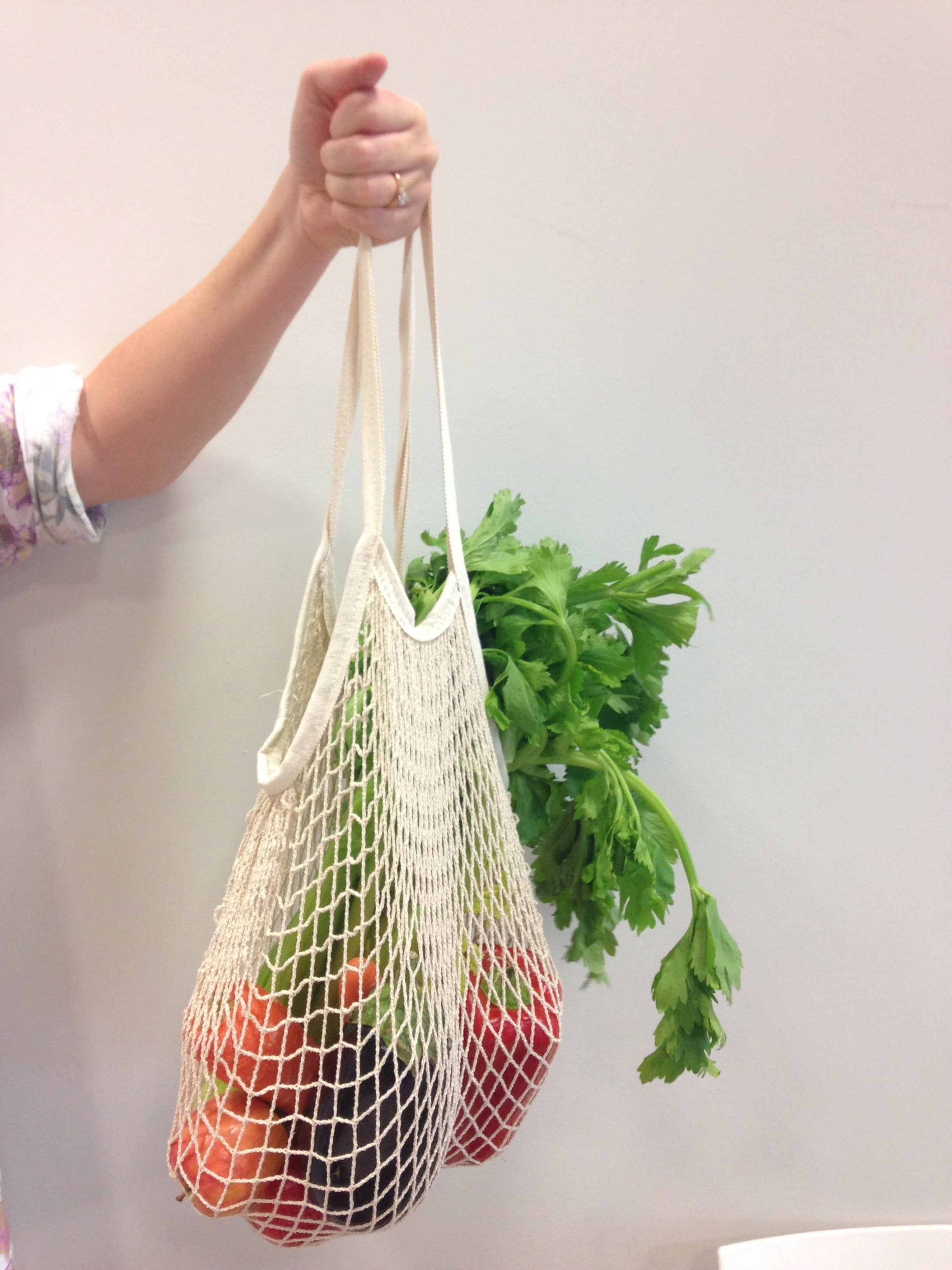 woman's arm holding an organic cotton produce bag containing fresh vegetables