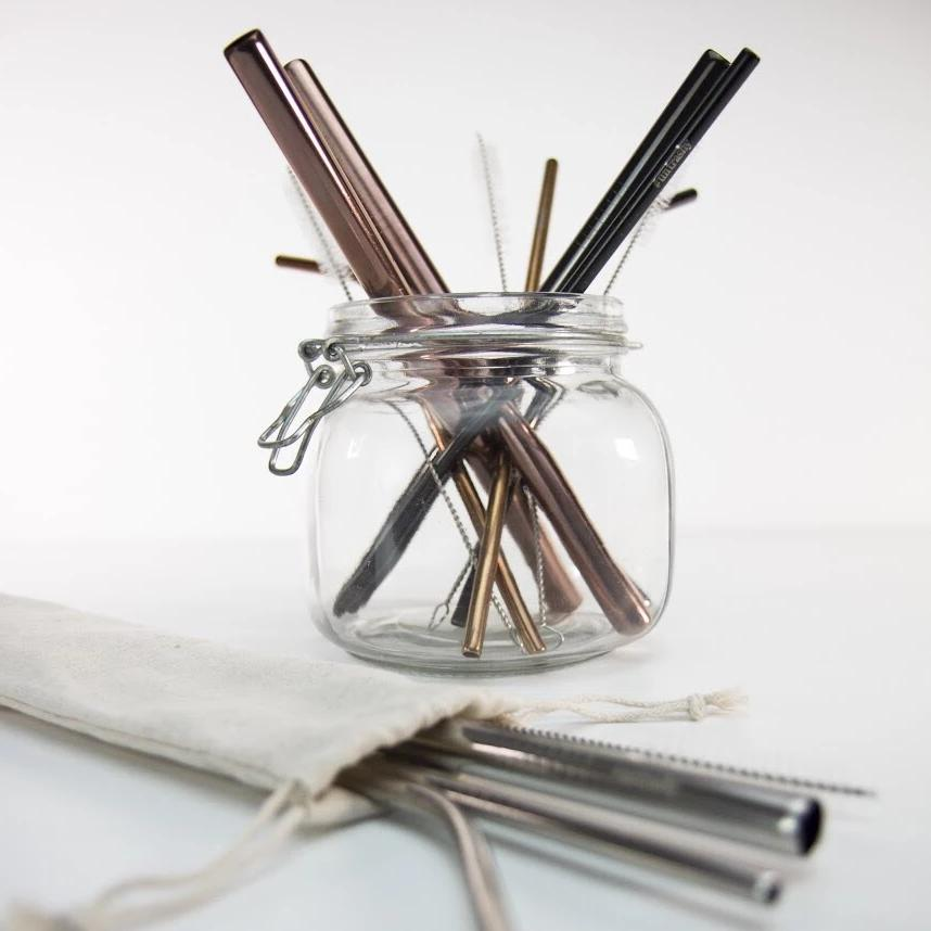 stainless steel drinking straws in different sizes and colours in a jar with a bag of straws in the foreground