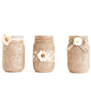 mason jar set decorated with gold glitter, ribbon and paper flowers