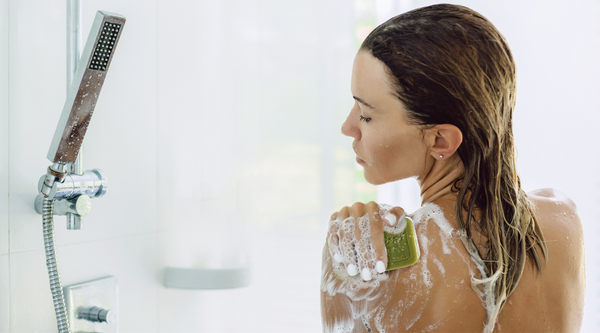 Woman exfoliating with Marie Ernst soap in shower