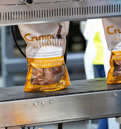 Assembly line showing a package of Crumps' on a conveyor belt.