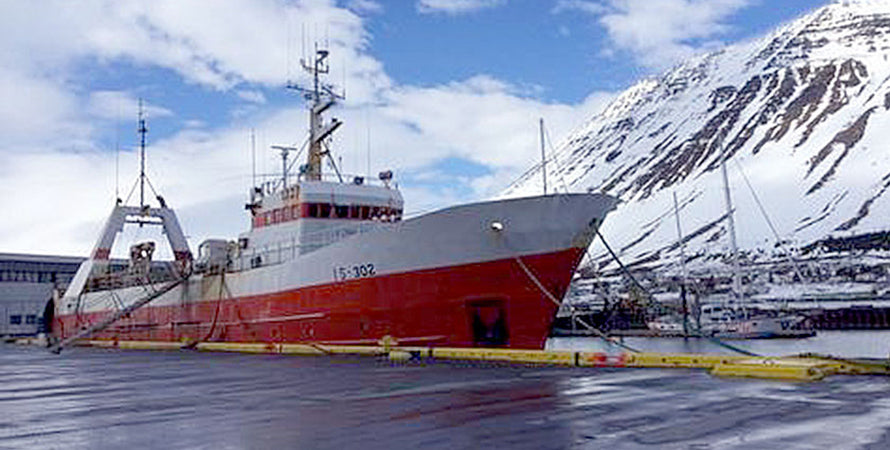 A picture of a large red and white commercial fishing boat docked