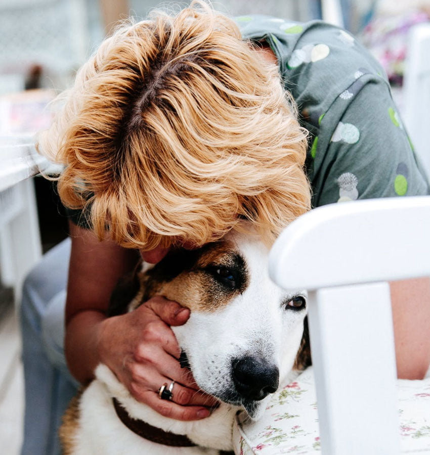 A blonde haired woman giving her dog a hug from above.