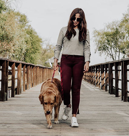 A girl walking her dog on a wooden slat pedestrian bridge.