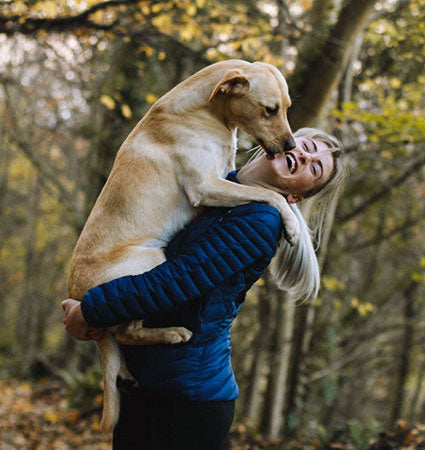 A girl on a hike holding her big yellow lab dog close on her chest.