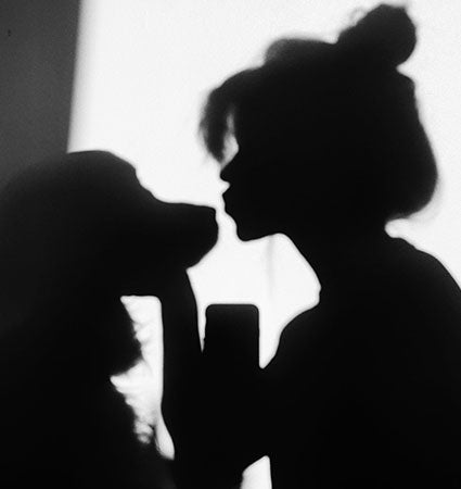 A sillouette of a woman and her dog.