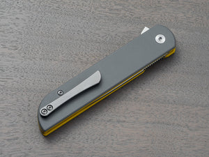Closeup of pocket knife with titanium clip and gray handle