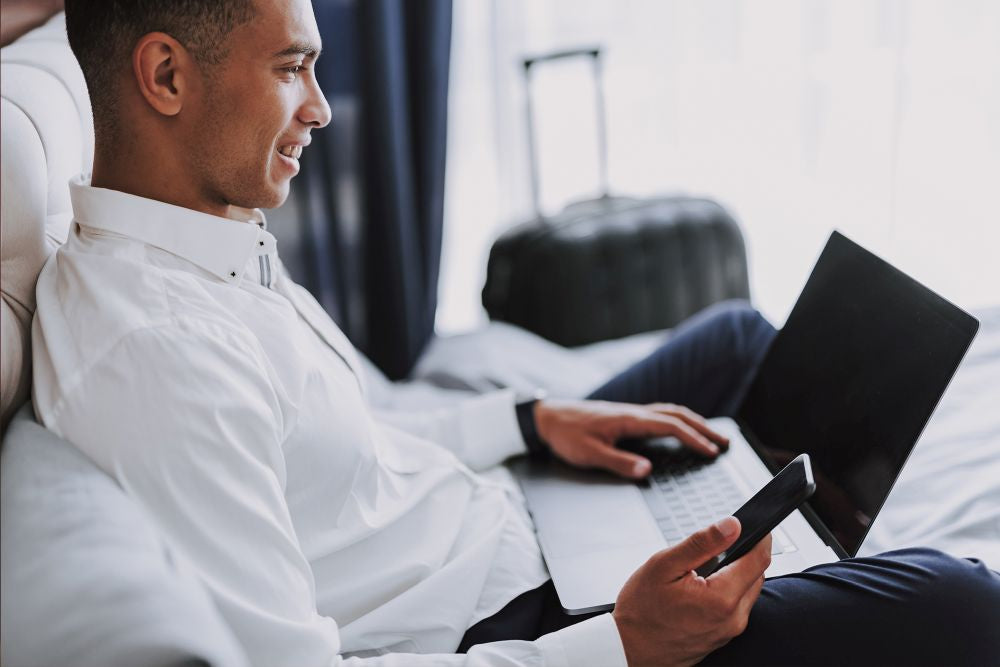 Man using a laptop and a phone in a hotel - Brandstand