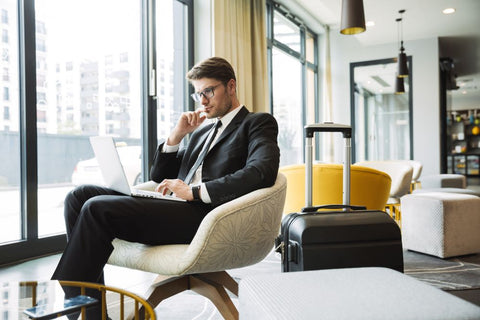 Hospitality technology trends - Using a laptop in a hotel lobby