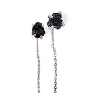 white gold prong-set raw black diamond earring close-up