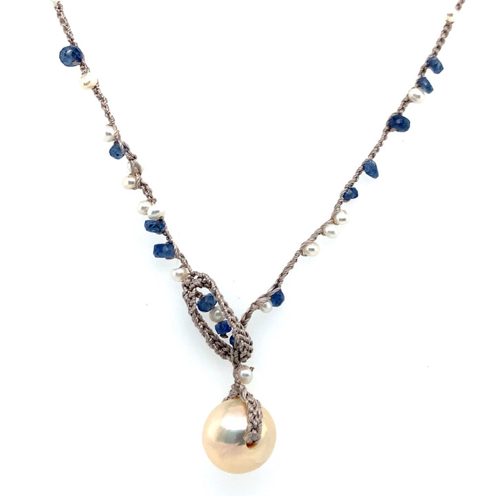 Delicate crocheted silk 18 inches in total length, but can be adjusted.  Freshwater pearls, and Montana sapphire rondelles, finished with a saucer-shaped freshwater pearl at drop.