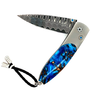 he blade is 'Wave' Damascus with VG-10 core; the one-hand button lock and the thumb stud are set with Kashmir blue topaz.