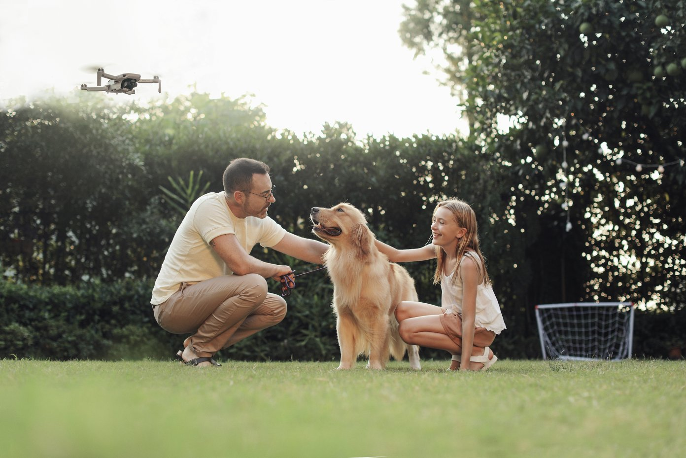 Family with dog and DJI Mavic Mini flying in background
