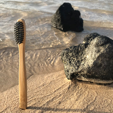 Bamboo toothbrush with charcoal bristles sat in the sand next to a rock on the beach