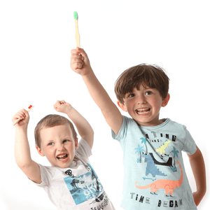 Two children with kids bamboo toothbrushes