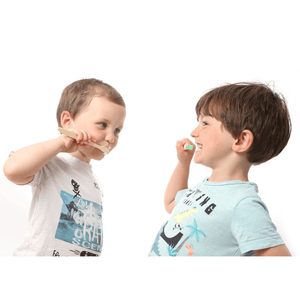 Two children brushing their teeth with a bamboo toothbrush