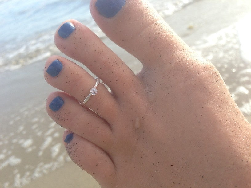 CZ Solitaire Sterling Toe Ring shown on a foot at the beach