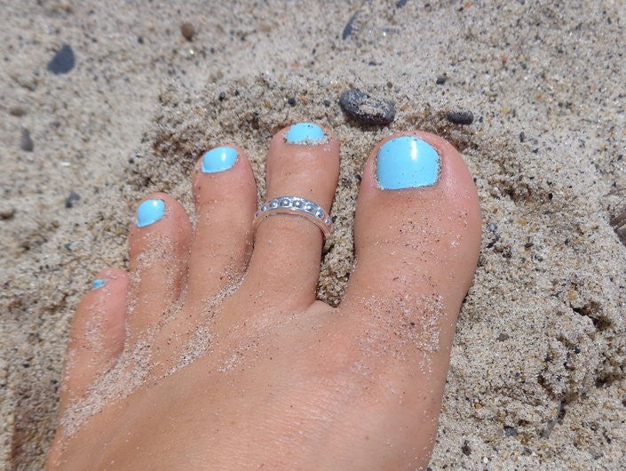 Bee Bee Wide Sterling Toe Ring shown on a foot in the sand