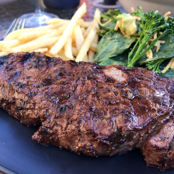 Jerk marinaded steak and fries with broccolini salad