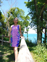 Brandy Searcy standing next to Lake Michigan in a pink color block dress